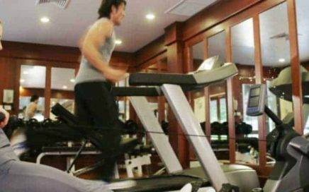 Man and woman using indoor gym equipment to workout