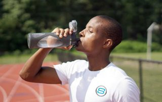 Man on a track drinking water