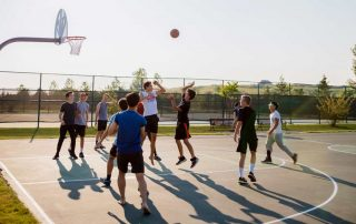 Group of men playing a casual basketball game in a park
